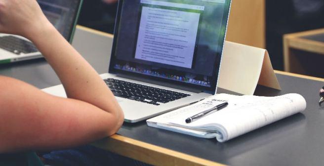 Pessoa estudando com um notebook e um livro sobre a mesa